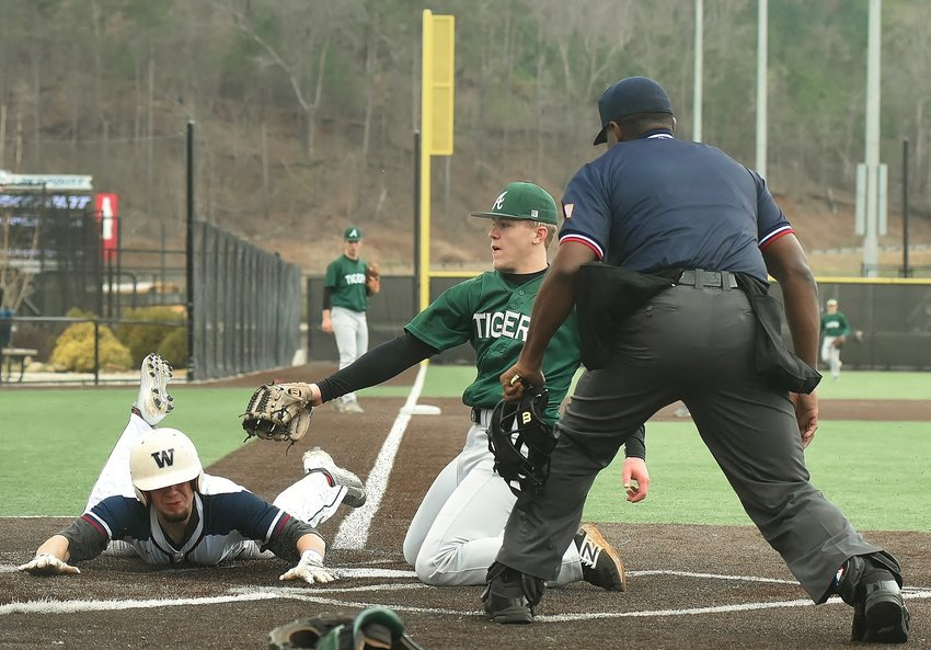 Woodland's Koby Stansel scores on a wild pitch as Adairsville pitcher Jacob Ray covers home plate.