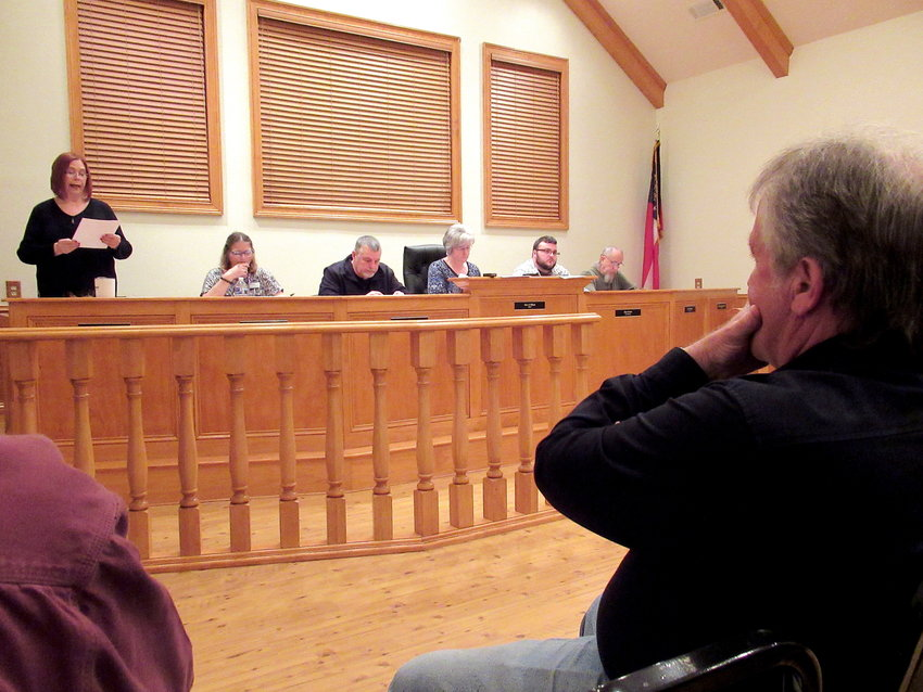 White City Clerk Robin Deal, standing, reads the agenda at Monday evening's city council meeting.