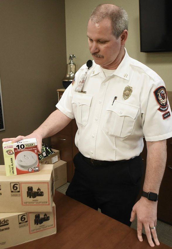 Cartersville Fire Department's fire marshal, Mark Hathaway, examines one of the smoke alarms that is available to the public.
