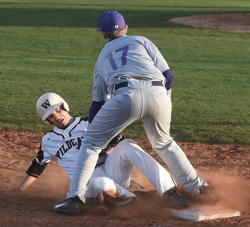 Woodland runner Zach Wilson slides safely into third base ahead of the tag of Hiram's Owen Ragsdale during Wednesday's home game against the Hornets. Wilson finished 1-for-4 and scored a run in the Wildcats' 9-4 victory.
