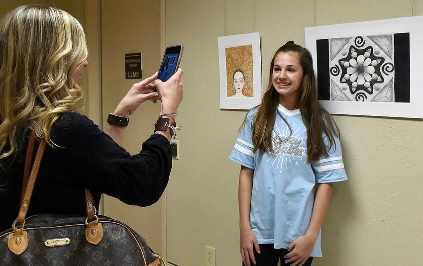 "As her mother, Mande England, takes a photo, Cartersville Middle art student Ailee England stands next to her piece titled  ""Twilight Shadows"" at the Middle and High Schools Art Exhibition in the Borderlands Gallery at the Booth Western Art Museum."