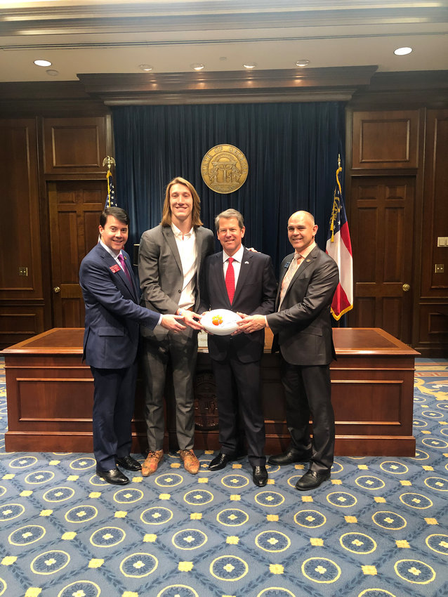 Trevor Lawrence — joined by State Rep. Matthew Gambill, left, and State Sen. Bruce Thompson, right — presents a signed Clemson football to Georgia Gov. Brian Kemp.