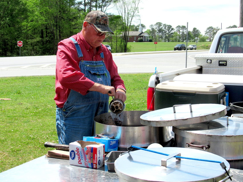 Kenneth Vaughan, owner of Pop's Fresh Boiled Peanuts and Fresh Pork Skins, fills a customer's order on Thursday.