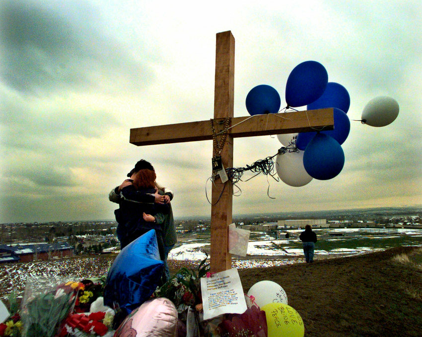 In this April 24, 1999, photo, unidentified students embrace each other at a makeshift memorial for their slain classmates at Columbine High School on a hilltop overlooking the school in Littleton, Colorado. Twelve students and one teacher were killed in a murderous rampage at the school on Tuesday, April 20, 1999, by two students who killed themselves in the aftermath.