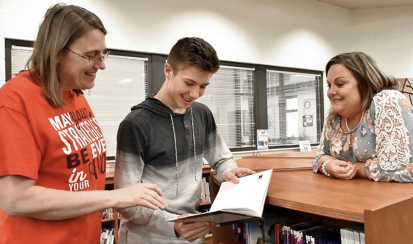 As Adairsville Elementary media specialist Regina Hicks, left, and Principal Melissa Zarefoss look on, Adairsville Middle eighth-grader Brett Lance thumbs through one of the books the school was able to purchase due to his fundraising efforts.