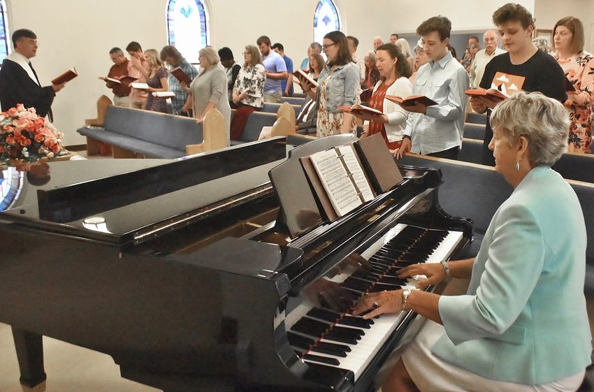 Bartow Cumberland Presbyterian Church Pastor Mark Rackley, left, and pianist Clarissa Bagwell lead the congregation in song May 12. The church will celebrate its 150th anniversary Sunday.