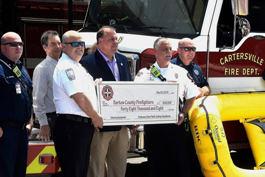 Bartow County Fire Chief Craig Millsap, Cartersville Mayor Matt Santini and Cartersville Fire Department Chief Scott Carter hold a replica check representing grants to both departments, totaling $48,008 worth of equipment, from the Firehouse Subs Public Safety Foundation.