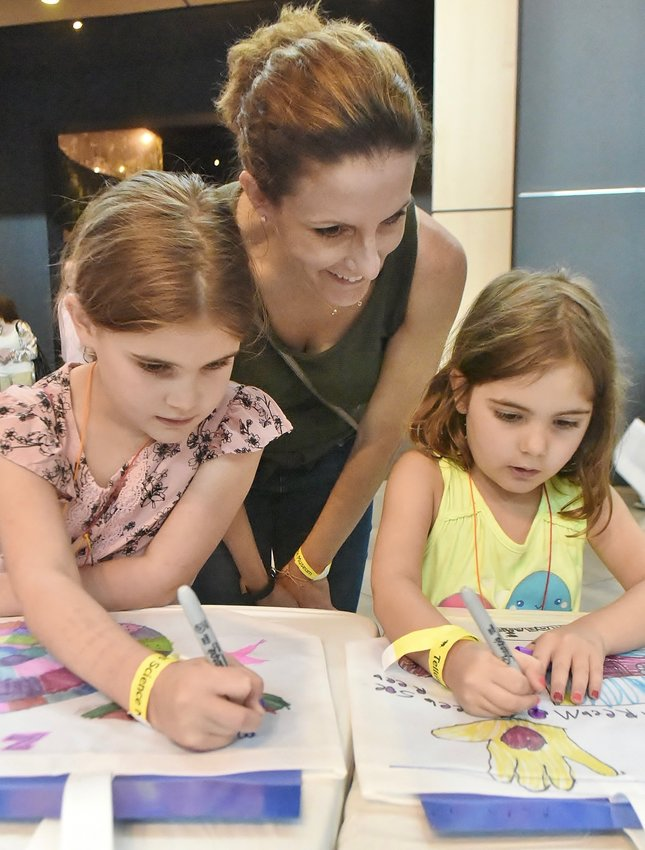 Julie Reed, center, of Marietta, watches as her daughters Zoe, 7, left and Phoebe, 5, customize tote bags with geological drawings at RockFest 2019 at Tellus Science Museum Saturday and Sunday. Nearly 4,000 guests attended the annual event, where more than 25 vendors displayed gems, minerals, fossils and jewelry, and there were geology-themed activities for children in the museum's Great Hall.