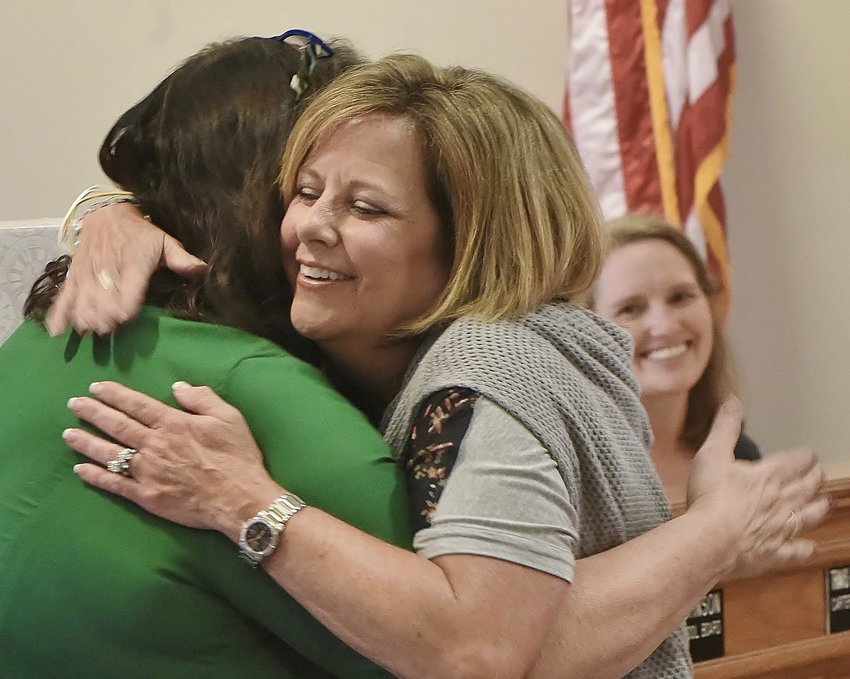 As Cartersville City School Board member Louise Panter, right, looks on, Linda Linn, center, hugs board President Kelley Dial at Monday's board meeting, at which the system's 2019 retirees were recognized. Linn retired after 30 years as an educator, most recently at Cartersville Primary School.