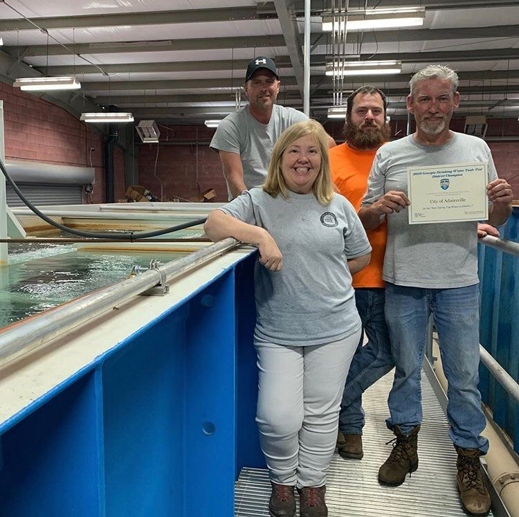 Leslie McClure, from left, Lisa Eury and Lanny Allen accompany Danny Tatum as he holds Adairsville Water Department's District 1 championship award for Best Tap Tasting.