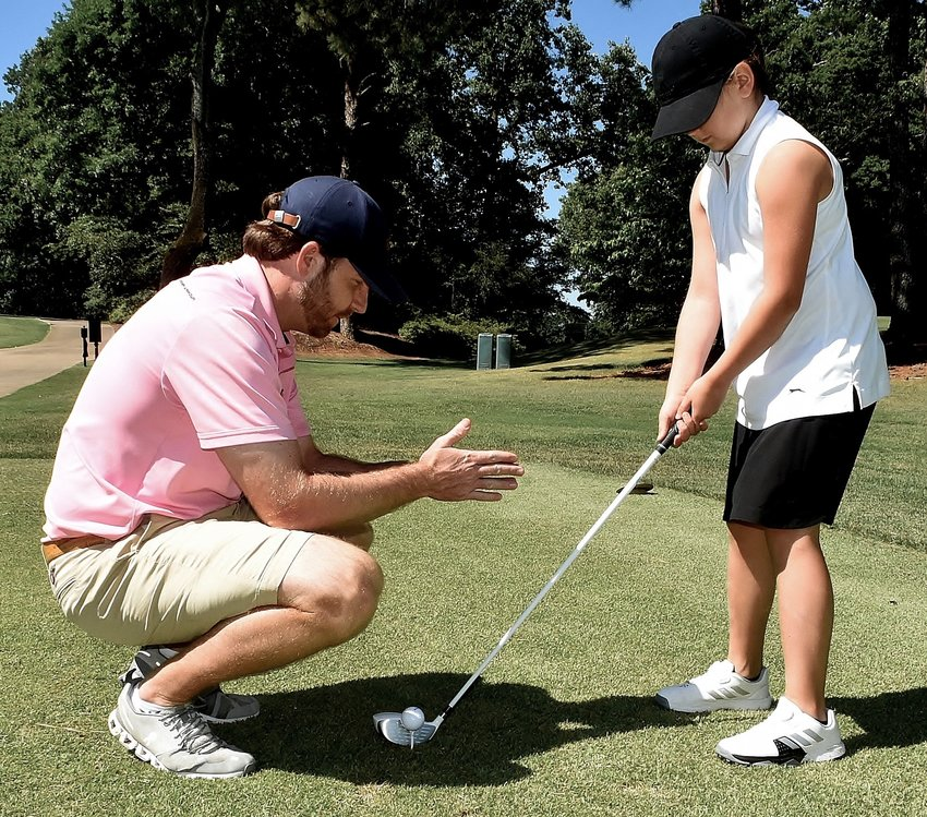 Bill Hassell works with Sydney Satterfield during a youth camp Friday at Cartersville Country Club. Hassell is director of instruction at the club, as well as head golf professional and lead instructor for the Scott Hamilton Golf Academy.