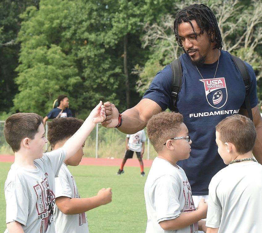 Atlanta Falcons player and Adairsville native Vic Beasley Jr. fist bumps a camper during his USA Football FUNdamentals clinic Saturday at Adairsville Middle School.