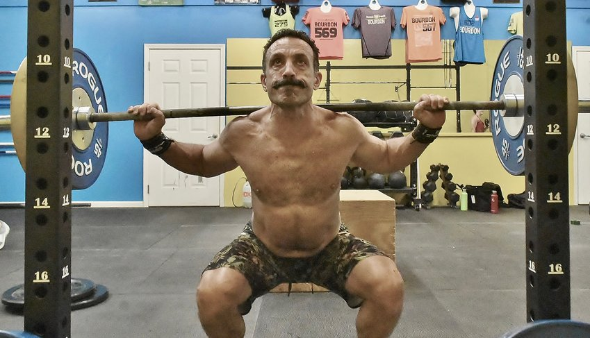 Carl Giuffre works on barbell back squats during a workout Wednesday at CrossFit Adrenaline in Cartersville.