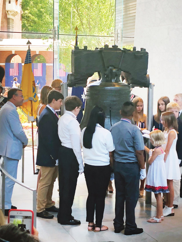 Woodland High rising senior Dallas Adams, left in dark jacket and tan pants, taps the Liberty Bell during a Fourth of July ceremony in Philadelphia. The 17-year-old is a direct descendant of Declaration of Independence signer Thomas Heyward Jr.
