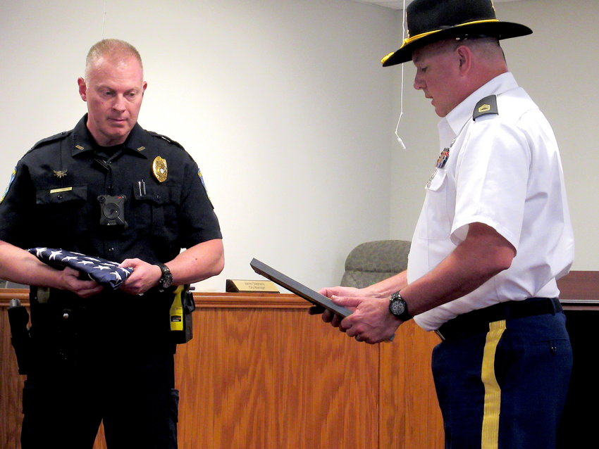 Army Sergeant First Class David Brockwell presents Euharlee Police Department officer Tim Merrell with an American flag flown in combat at Tuesday evening's Euharlee City Council work session.