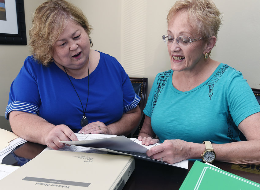 CASA Director Ava Lipscomb, left, shows volunteer Pam Lord the organization's new training manual more than four years ago.