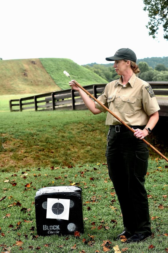 Etowah Indian Mounds naturalist Jackie Kane loads a dart into a bamboo tube, which is used as a blow dart gun.