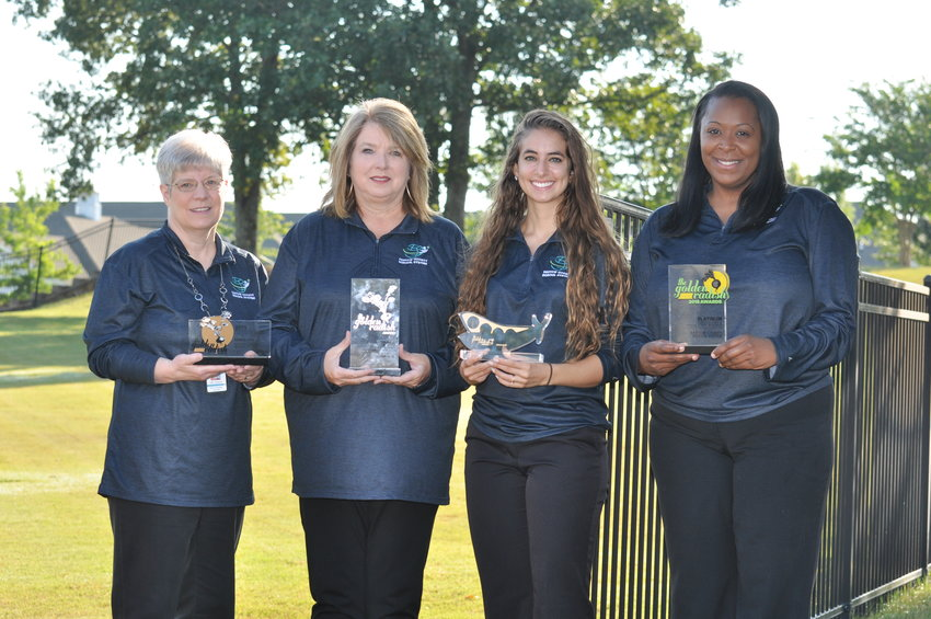 Showing off the past four Golden Radish awards won by the Bartow County School System nutrition department are, from left, school nutrition technology specialist Kellie Thompson, holding the 2015 bronze award; school nutrition accounting specialist Vicky Wade, 2016 silver award; School Nutrition Coordinator Emily Miller, 2017 gold award; and School Nutrition Director Oreal Oladele, 2018 platinum award.