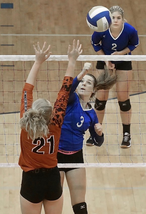Cass junior Avery Morlot hits the ball over the net as teammate Riley Nelson (2) watches during Tuesday's home match against Kell.