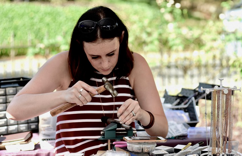 Meagan RuBright, owner of the The Brass Pineapple, carefully handstamps a ring at her booth at last year's Arts Festival at Rose Lawn. The 44th annual arts festival will be held Saturday and Sunday, September 21 and 22, on the grounds of Rose Lawn Museum.