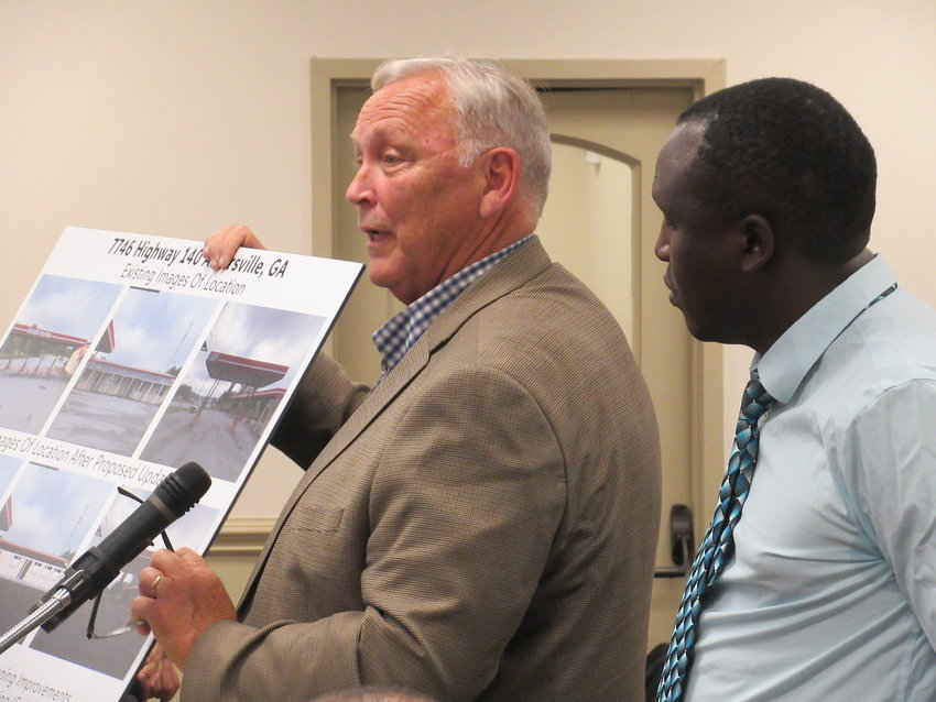 From left, Daniel Deems shows conceptual artwork for a new truck stop off Highway 140 in Adairsville proposed by Woodstock entrepreneur Alfonce Chelimo.