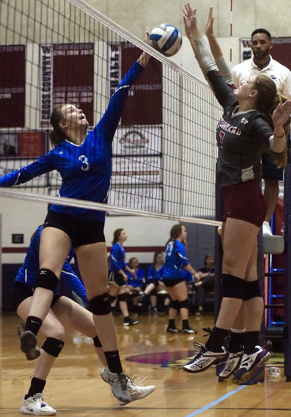 Cass junior Avery Morlot, left, tries to tip the ball over the net, as Woodland senior Grace Webb (7) and a teammate attempt a block during Thursday's match at Woodland. The Wildcats won in three sets. Both teams also defeated Gordon Central in the tri-match.