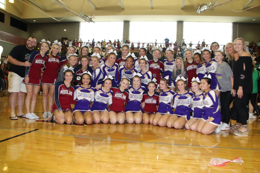 The competition cheer teams from Woodland and Cartersville pose for a photo Saturday at Allatoona. The Wildcats finished first in Class 5A — the team's third win in as many competitions this season — and the defending state champion Canes were victorious in Class 4A.