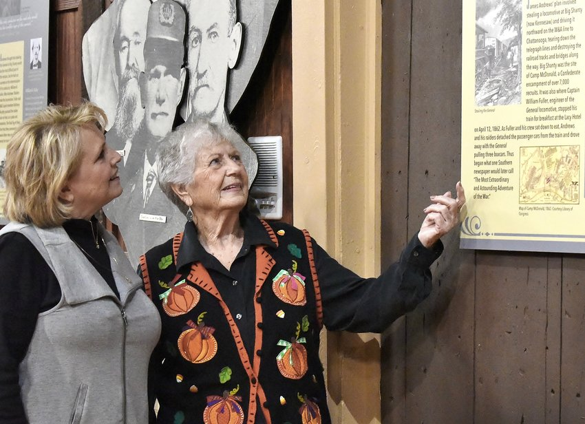 The Adairsville Depot History Museum and Welcome Center's Joyce Culberson, right, points out historical facts found on one of the informational boards in the museum to Debbie Gatlin, of Canton. The information boards are part of the KSU permanent exhibit in the depot.