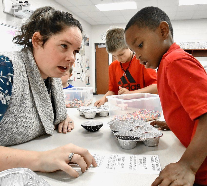 Adairsville Middle School STEM teacher Ashley Greenway, recipient of a presidential award as one of the nation's best STEM teachers in grades K-6, works on division problems with third grade student Davion Jackson.