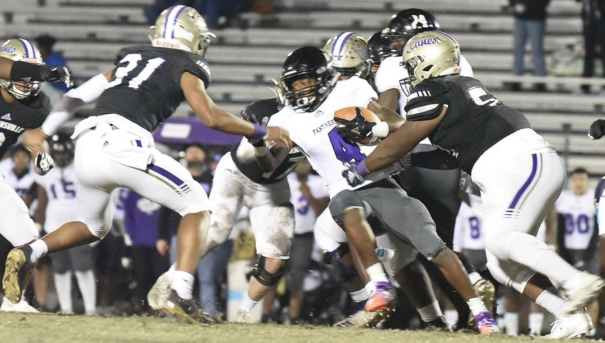 Cartersville senior La'Kwayme Jupiter, right, wraps up a ballcarrier as several other Canes converge during Friday's win. The victory guaranteed Cartersville its eight consecutive region championship.