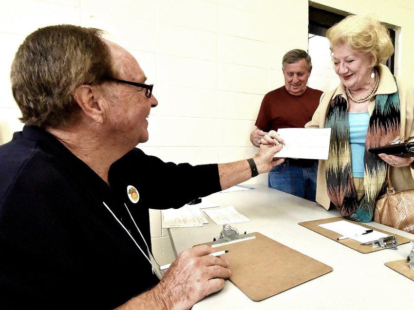 Poll worker Jerry Gravley hands Cartersville resident Mina Harper a voter registration card Tuesday at the Cartersville Civic Center.