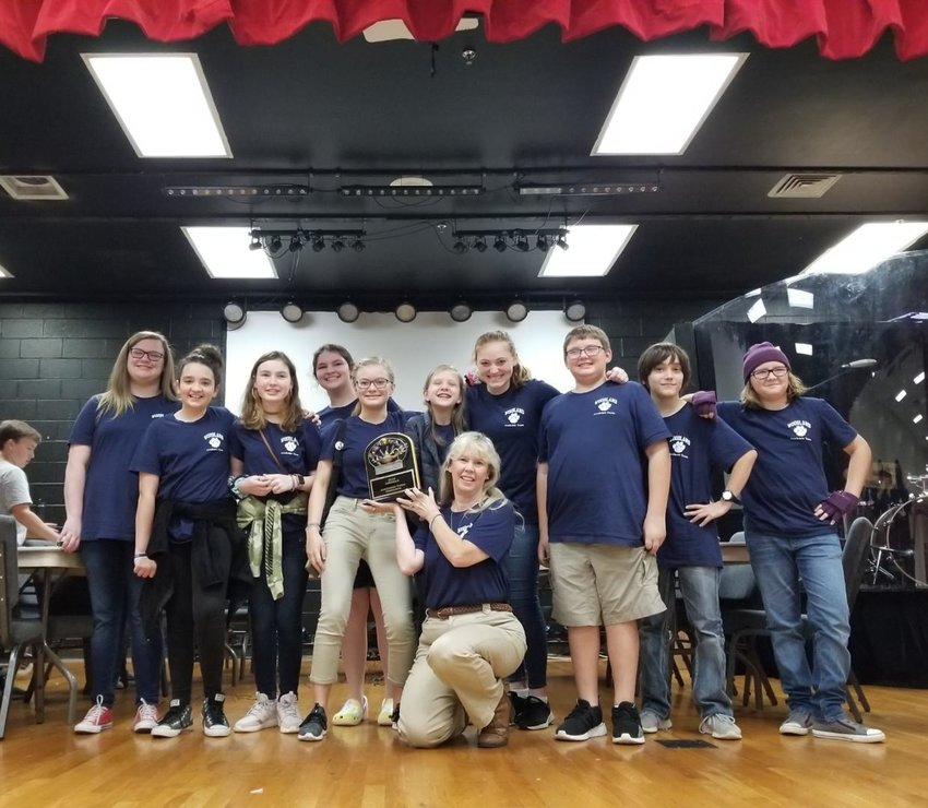 Woodland Middle School's academic team, coached by Dr. Cindy Schwartz, shows off the regional championship plaque it won last month.