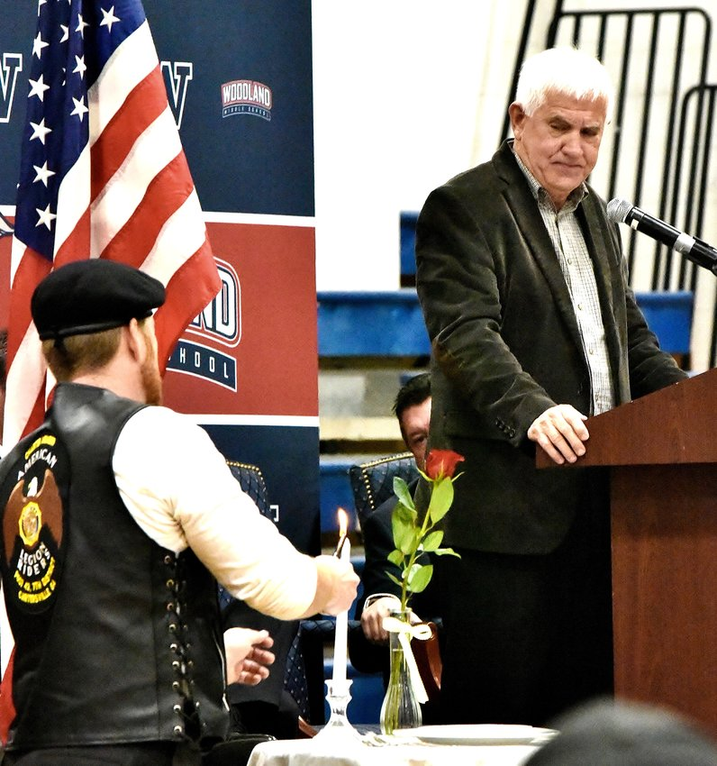 Reverend Steven F. Lyle looks on as U.S. Army veteran Kris Dittrich lights the candle on the Missing Man Table during the Veterans Day Ceremony Monday at Woodland Middle School. A missing man table is set up in military dining facilities of the United States Armed Forces in honor of fallen, missing or imprisoned military service members.