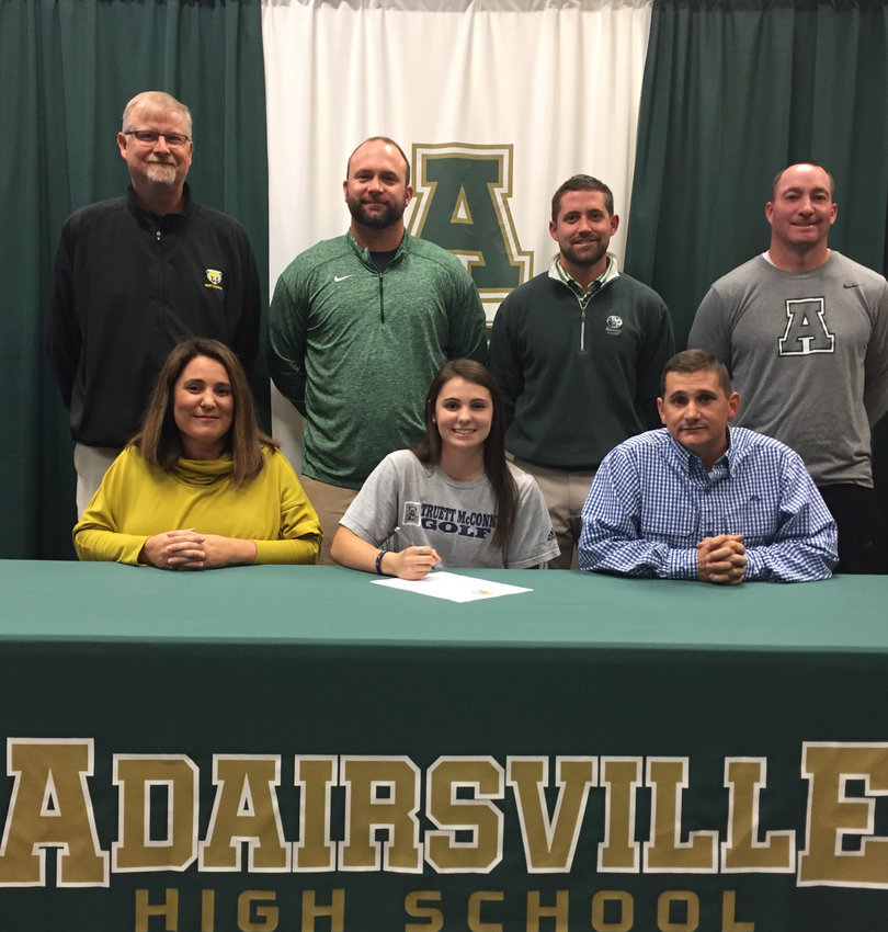 Adairsville High senior Cortni Jacobs signed to play golf at Truett McConnell in Cleveland, Georgia, Wednesday in the AHS media center. On hand for the ceremony were, from left, front row: Elizabeth Jacobs, mother; Terry Jacobs, father; back row, Steve Patton, TMU coach; Kurt Scoggins, AHS coach; Chase Rutledge, Barnsley Gardens golf pro; and Jon Cudd, AHS coach.
