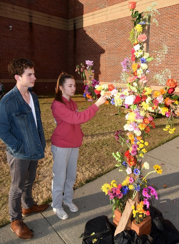 Woodland High School sophomore Logan Bennett watches as senior Bailee Bozeman places a flower on the memorial outside the school's Performing Arts Center in memory of Eddie McPherson, the WHS drama teacher who died Sunday.