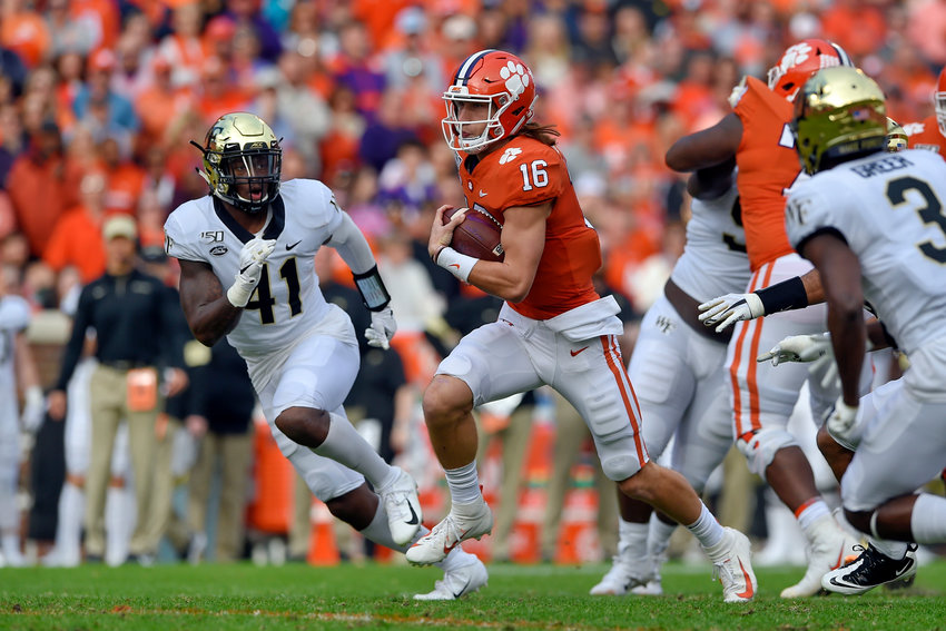 Clemson quarterback Trevor Lawrence (16) scrambles out of the pocket while defended by Wake Forest's Ja'Corey Johns (41) Saturday in Clemson, South Carolina. Lawrence and Johns are both former all-state players for Cartersville High.
