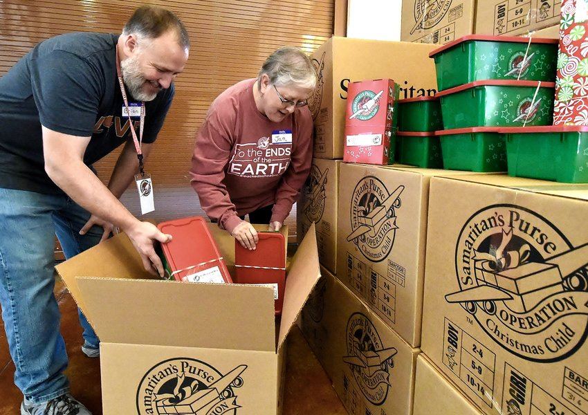 Jan Burkett, Operation Christmas Child drop-off team leader, loads a box of gift-filled shoeboxes with volunteer Brian Bunce at Cartersville First Baptist Church Monday.