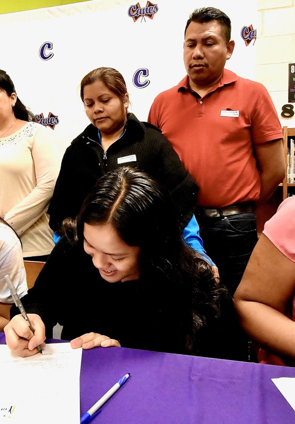 As her parents, Silvia Delores and Ignacio Vargas watch, REACH scholarship recipient Jacqueline Vargas signs her contract at the REACH Georgia  Signing Ceremony Tuesday morning at Cartersville Middle School.