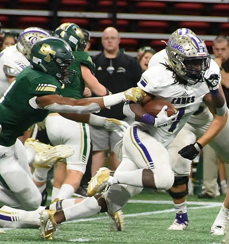 Cartersville senior running back Marcus Gary escapes the grasp of a Blessed Trinity defender during the Class 4A state championship game last December at Mercedes-Benz Stadium. The Canes and Titans will be Region 7-AAAAA foes, beginning with the 2020-21 school year.