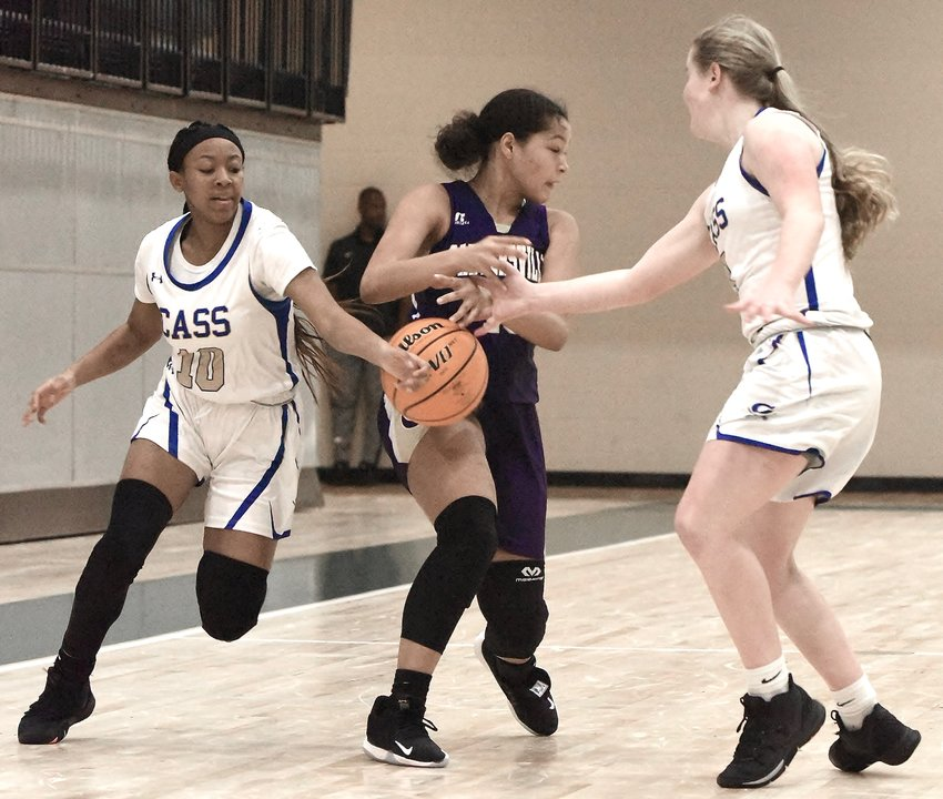 Cass sophomore Keara McDaniel (10) and Haley Johnson combine to steal the ball from a Cartersville player during a semifinal of the AHS Tiger Christmas Clash Saturday in Adairsville.