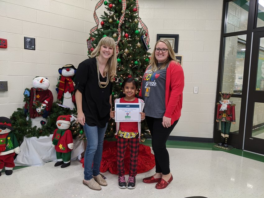 Deanna Mathis, left, community outreach director for Shaw Industries, presents the third-place elementary division prize for Shaw's Student Art Contest to Adairsville Elementary second-grader Zeel Patel as the young artist's teacher, Sarah Collum, looks on.
