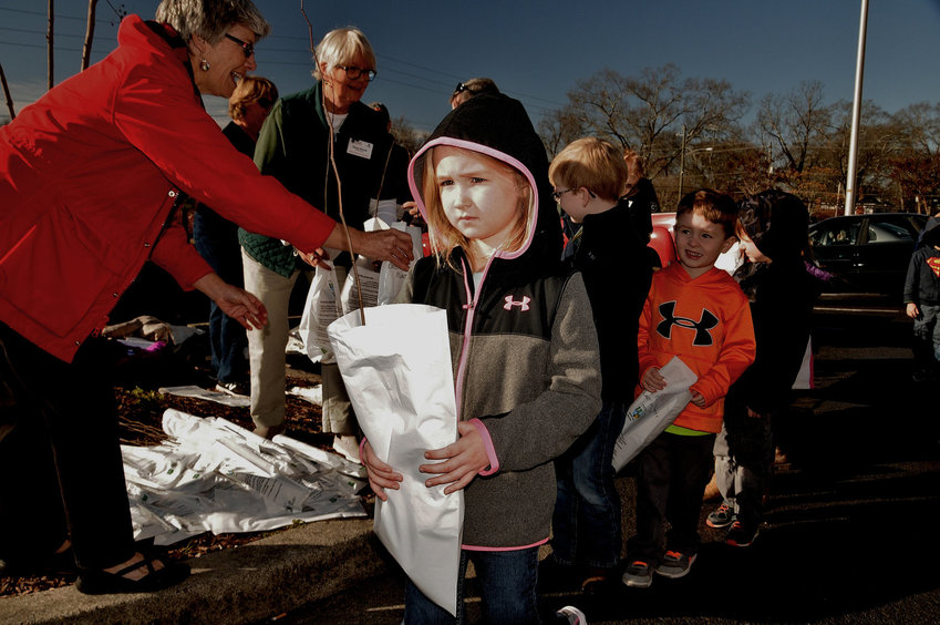 Children receive tree seedlings at a 2018 Arbor Day celebration.