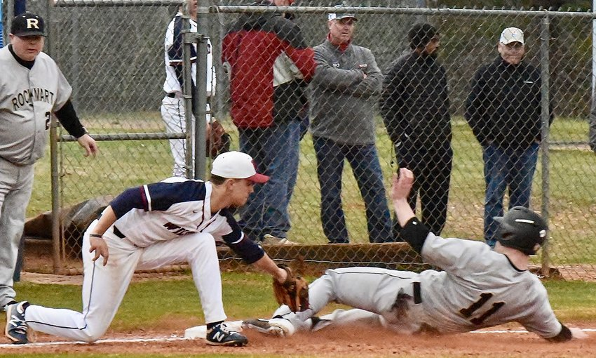 Woodland third baseman Zach Wilson tags Rockmart's Reed Couch a fraction too late as Couch slides safely into third base during Monday's game at Woodland.