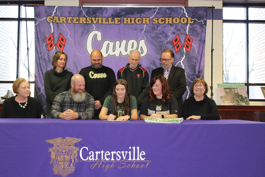 Cartersville's Savannah Warren, center, signed to play softball for East Georgia State College. Pictured at the signing ceremony in the Cartersville High media center are, from left, front row, Brenda Warren, Eric Warren, Meredith Warren, Georgina Howe; back row, Shelley Tierce, Dutch Cothran, Mike Talley and Darrell Demastus.
