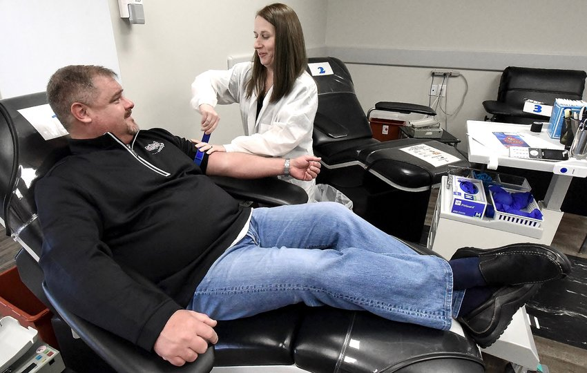 Blood Assurance Donor Care Specialist Ava Voyles prepares donor Corey Sanford to give blood at the Main Street Shopping Center Blood Assurance facility in Cartersville.