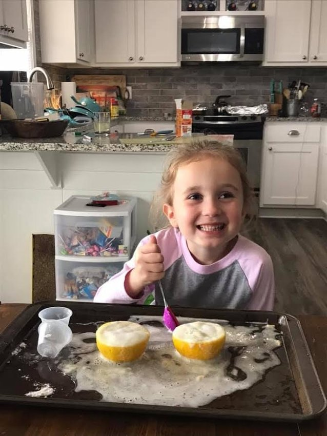 As part of her digital learning experience, Kids & Co. pre-K student Lexi Grace Petersen, 4, works on a science experiment at home last week.