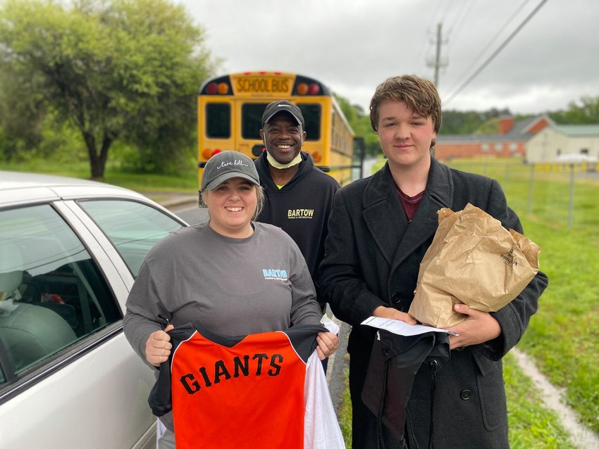 Bartow County Parks and Recreation staff members Haley Hood and Dennis Knowles, center, delivered gifts to Bartow students during Monday's meal delivery.