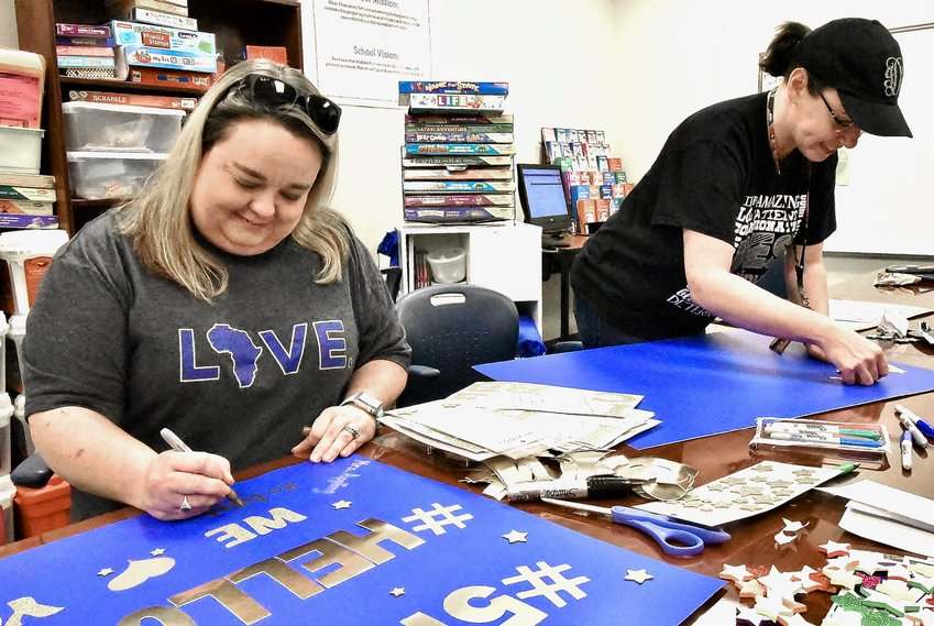 White Elementary School fifth grade teachers Jennifer Appling, left, and Jennifer DeHart prepare signs that they will display as the school's graduating fifth graders are recognized and honored in the upcoming Warrior Wave.