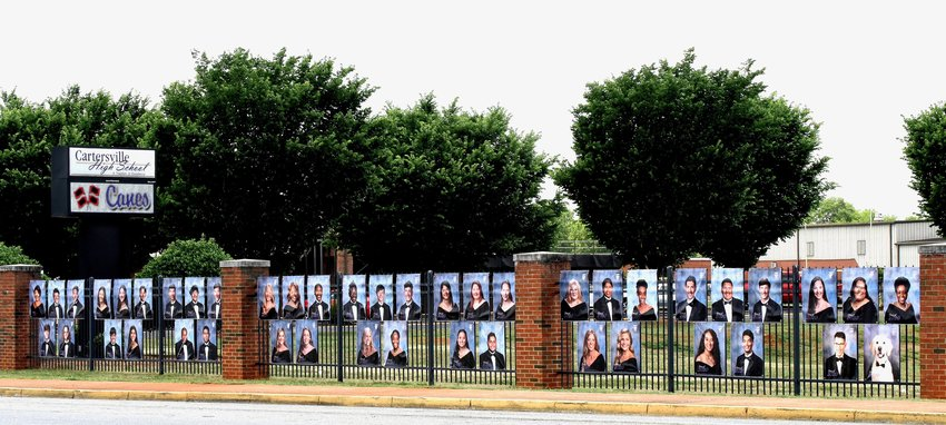The fence along Church Street in front of Cartersville High School displays a portrait of each graduating senior, as well as Riley, Israel Satterfield's service dog, bottom right.