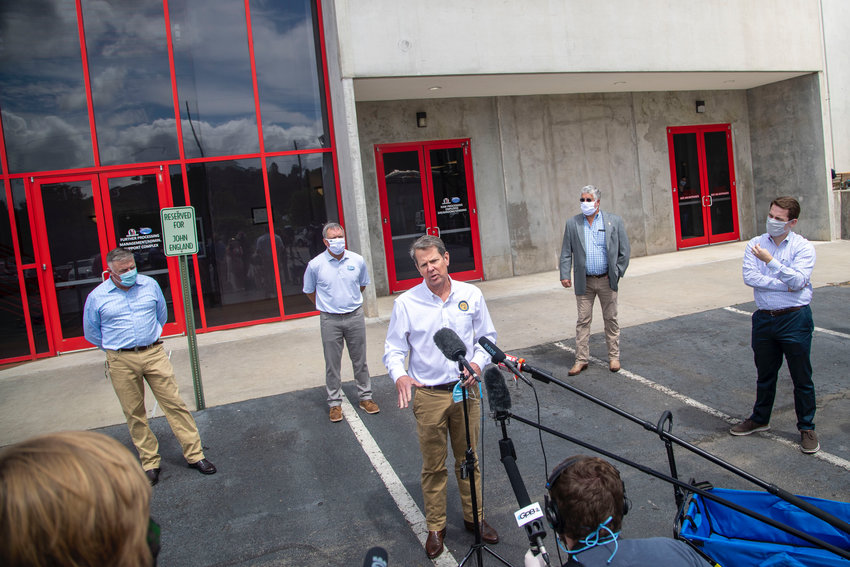 Governor Brian Kemp, center, makes a statement and answers questions following a tour of Fieldale Farms while visiting Gainesville Friday.